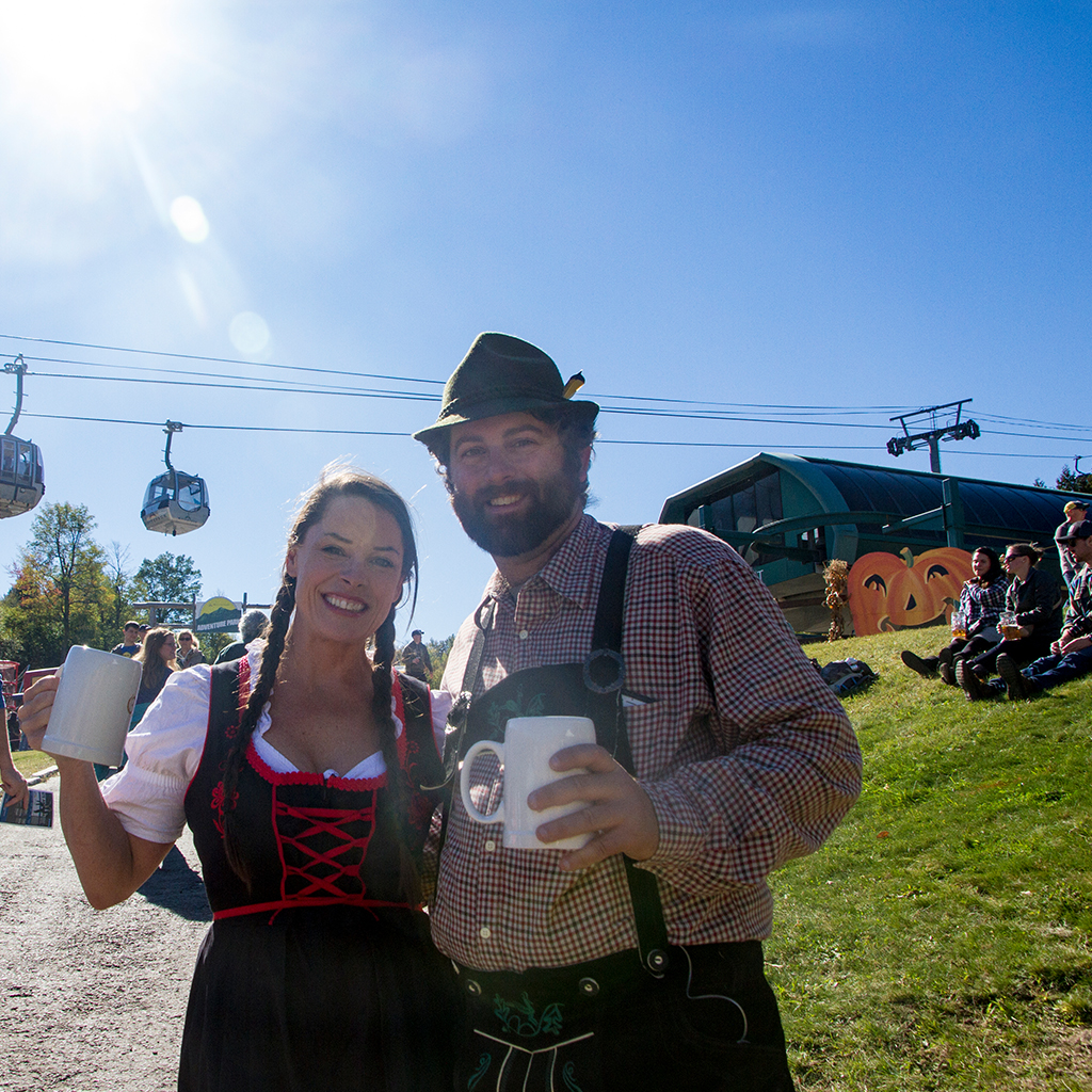 A couple dressed in German garb with mugs at the Whiteface Oktoberfest.