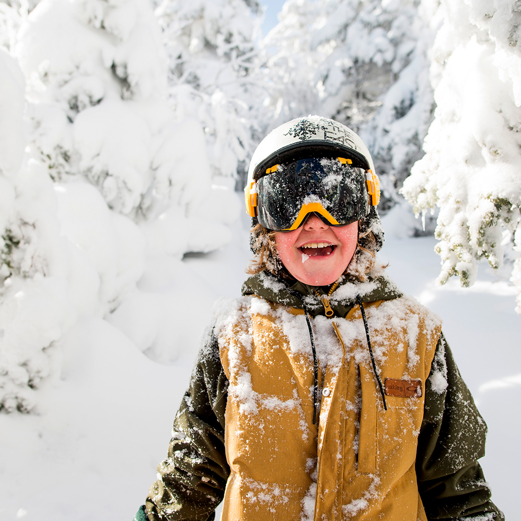 Happy child with snow-covered trees in the background.