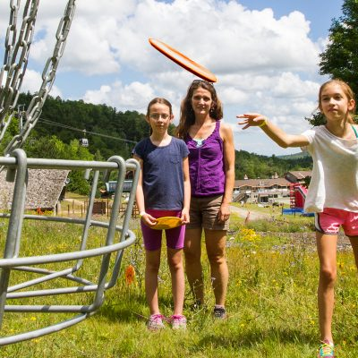 An adult female and two young girls playing Disc golf at Whiteface.