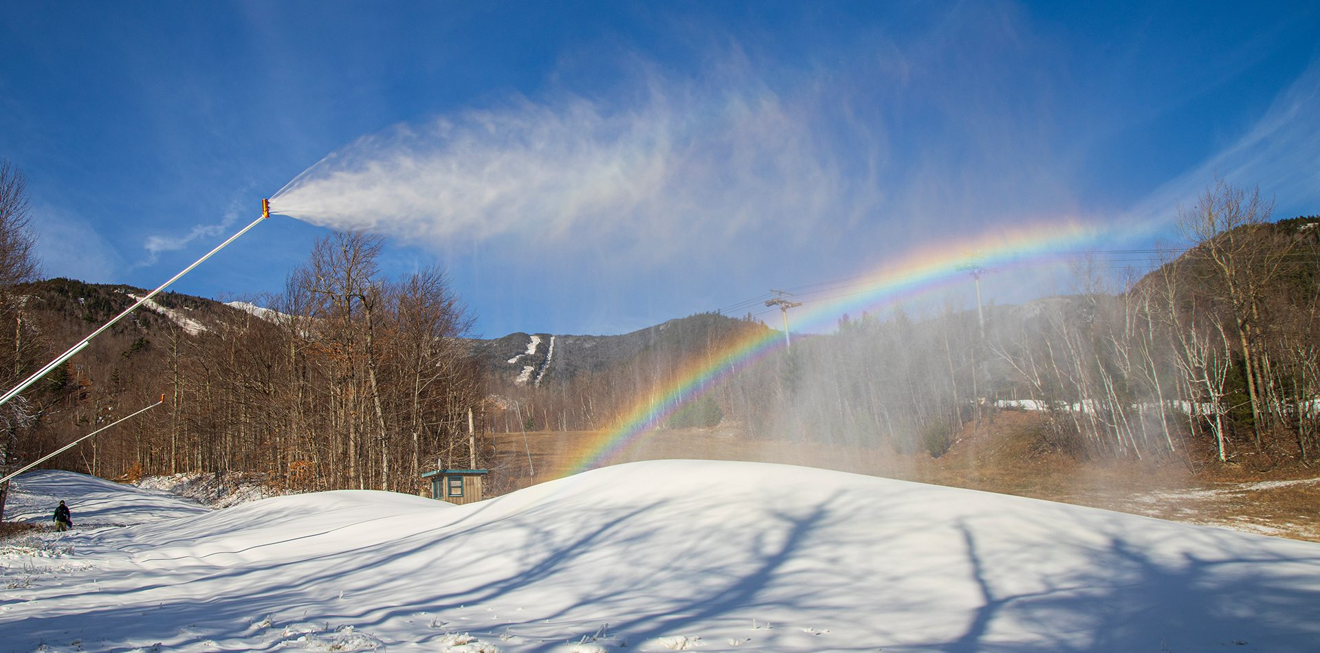 Snowmaking rainbow on Wolf trail with Whiteface in the distance.