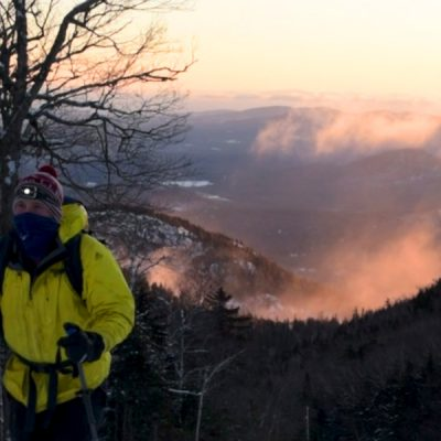 Man using uphill rout at Whiteface with the sunrise pink in the background.
