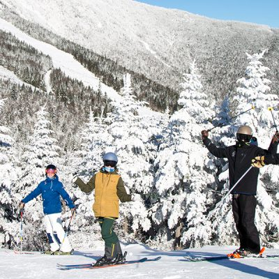 Small group of young people on top of Little Whiteface with snow covered trees in background.